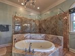 The whirlpool tub, glassed-in double-head shower, and private water closet are all accented with Italian marble.