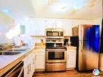 Fully stocked kitchen with dishwasher and refrigerator/freezer