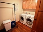 Lower level laundry room with front loading washer/dryer and hanging rack