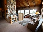 Sitting area off living room with two rocking arm chairs, a game table for 4 and picture windows with ocean and...