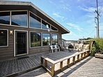 Large dual level, ocean view deck with patio chairs, portable fire pit and glass deck siding for the west winds