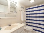 Hall bathroom with a tub/shower, open to hallway but can be closed off to north guest bedroom