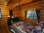 Snuggle into a spruce log master bedroom