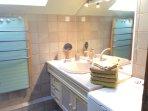Salle de bain commune : baignoire, lavabo, sèche serviettes, sèche cheveux, lave-linge.