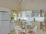 Modern kitchen with dining table for four, AC, fan, window. Fridge and freezer with ice cube maker