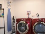 Spacious laundry room with front loading machines as well as iron and ironing board