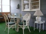 Screen porch has table and chairs and rocking chairs