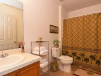 The 1st floor ensuite bathroom with bath, shower, sink, hairdryer, straighteners