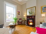 Spacious Living room with high ceiling and oak floor. Original fireplace for log fires.