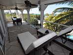 Great views from living room deck with lounge chairs and teak dining table