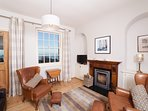 The living room in Beach Cottage has a log fire and stunning sea views