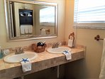 Master bathroom with partial view of lake, dual sinks, walk in shower with pebble floor, updated