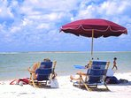 Sitting on beach.  Condo equipped w chairs, umbrella, cooler and beach toys