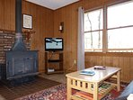 Our Living Room Features a Large Wood-Burning Stove, a Flat Screen TV, and Comfy Furniture