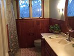 Full bath with shower, done in cherry paneling on the walls