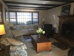 The family room has 2 large couches, 2 lounge chairs, fireplace  and a TV set.