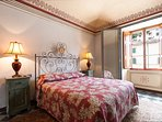 The red bedroom is very large and looks onto the piazza