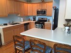 Fully stocked kitchen with new stainless steel appliances and breakfast bar