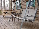 The Back Deck Features a Swing and a Picnic Table, and Looks Out Into the Forest