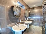 The en suite shower room is fully tiled, with walk-in shower enclosure with dual head shower and twin basins