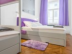 Violet room with two double beds and custom quality made bunk bed.