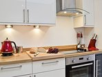 Kitchen with TV, electric oven & hob, microwave, fridge freezer & washer/dryer
