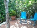 Sit in subtropical splendor. Patio at back of house overlooks Leitner Creek.