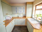 Spacious utility room adjoining the kitchen with 2nd fridge-freezer, microwave, washer and drier