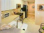 High-end appliances, under-cabinet lights, tile backsplash and Corian countertop