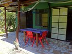 The large tiled patio is covered, table seats 4, hammock & wooden lounger.