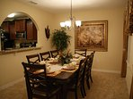 The formal dining room has a window opening to the kitchen and a large dining table.