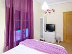 Dormitorio con suelo de tarima, cama de matrimonio y TV de 32'.