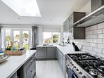 Range cooker, 90cm wide oven and 5 gas hobs. Kitchen island and breakfast bar.