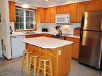 Lower level fully equipped kitchen with stainless steel appliances and a prep island/breakfast bar for 3