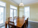 The large wooden dining table seats 8