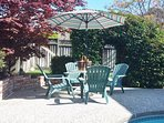 Umbrella with patio chair set by the swimming pool and spa