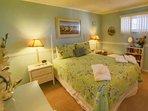 Second bedroom has queen bed, TV, direct bathroom access.