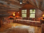 Cozy loft with seating that converts to 4 twin beds. Full bathroom is on main level.
