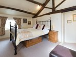 King Sized bed in the bedroom with a charachterful beamed vaulted ceiling