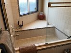 large sunk in tub with seat and shower