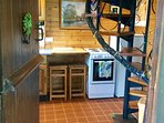 The kitchen with spiral staircase Firdige freezer, electric cooker and breakfast bar for 2.