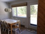 Open concept: dining adjacent to living room/kitchen.  Door leads out to deck.