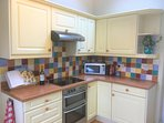 Fully equipped kitchen with integrated white goods.