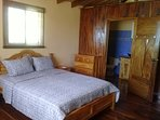 Queen size bed near bathroom teak frame and furniture. Native corotu wood floors and walls.