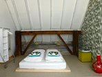 A spacious bedroom with a double bed. An extra bed can be added