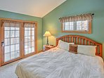The bright master bedroom offers deck access and a king bed.