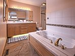 The master bathroom features a jetted tub, shower and dual sinks.