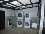 Two Washing machines and two dryers in laundry room