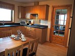 Dining kitchen with double oven, gas hob, fridge, freezer and dishwasher.  Leading to lounge.