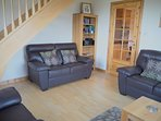 Lounge with oak, open tread staircase leading to bedrooms and bathroom.